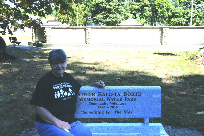 Esther Borte's daughter Christine Mershon sitting on the new memorial bench.